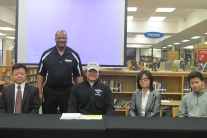 Song poses for a commemorative photo his parents, brother and coach after signing his letter of intent.