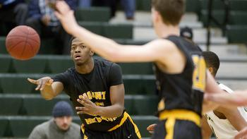 Senior Josh Bryant following through with a crisp pass to a teammate, while fellow senior Mark Smith finds open space to prepare himself for a possible jumper (Photo Courtesy of Jen Rynda / Baltimore Sun Media Group).